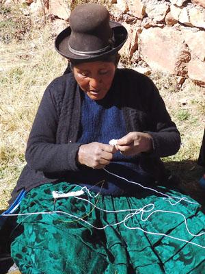 Yapuchiri woman knitting alpaca scarf